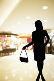 Silhouette of woman standing in a shopping mall ad holding a purse Stock Photos