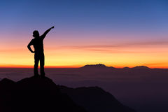 Silhouette of woman standing on the top of mountain and pointing Stock Photos