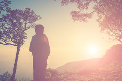 Silhouette of woman standing on top of the mountain waiting some Royalty Free Stock Photography