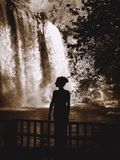 Silhouette of woman standing by waterfall Royalty Free Stock Image
