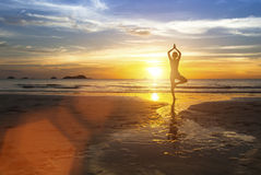 Silhouette of woman standing at yoga pose on the beach Royalty Free Stock Photos
