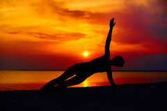 Silhouette of woman standing at yoga pose on the beach during an amazing sunset.  Royalty Free Stock Images