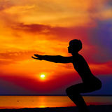 Silhouette of woman standing at yoga pose on the beach during an amazing sunset.  Stock Photo