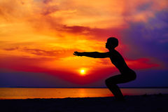 Silhouette of woman standing at yoga pose on the beach during an amazing sunset.  Royalty Free Stock Photos
