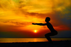 Silhouette of woman standing at yoga pose on the beach during an amazing sunset.  Royalty Free Stock Image