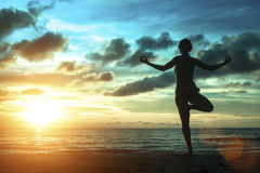 Silhouette of woman standing at yoga pose on the beach during an amazing sunset. Royalty Free Stock Photography