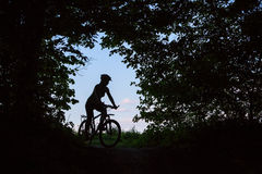 Silhouette of woman that stands with bike Royalty Free Stock Images