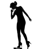 Silhouette woman stepping on personal weight scale. Full length silhouette in shadow of a young woman stepping on personal bathroom weight scale in studio on royalty free stock images