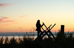 Silhouette of a woman on a stile at twilight time Stock Photo
