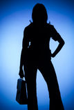 Silhouette of woman with suitcase Stock Image