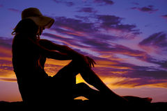 Silhouette woman sun hat sit hands on knees Royalty Free Stock Photo