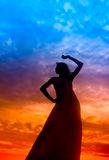 Silhouette of woman during sunset. Silhouette of woman performs as a dancer during sunset Stock Photo