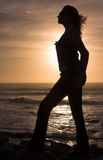 Silhouette of a woman at sunset. Silhouette of a blonde woman with long hair at sunset by the ocean Royalty Free Stock Photography