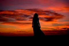 Silhouette of a woman in sunset with dress and hair blow by the wind. Romantic mood , gone with the wind , movie scene, red sky , free, relaxing time, book royalty free stock photo