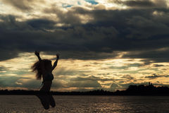 Silhouette woman at sunset jump on the beach Stock Photography