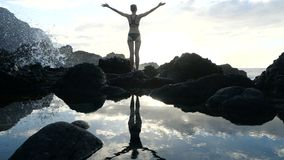 Silhouette of a woman at sunset observing waves and raising arms in the air. Cinematic slow motion. Silhouette of a woman at sunset observing waves and raising stock footage