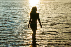 Silhouette woman at sunset in water Royalty Free Stock Image