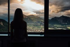 Silhouette of woman in sunshine at window with view on sunset in mountains stock photos
