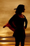 Silhouette woman super hero cape stock photo