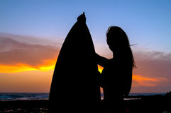 Silhouette of the woman with the surf board on the sunset Royalty Free Stock Image