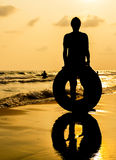 Silhouette of woman with swim ring on beach Stock Photos