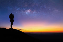 Silhouette of woman is taking the milky way photo on top of mountain Royalty Free Stock Images