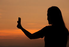 Silhouette of woman taking photo with mobile phone Royalty Free Stock Images