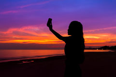 Silhouette of woman taking photo of sunset with mobile phone, at royalty free stock image