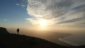 Silhouette of a woman taking pictures of an incredible sunset on the top of a mountain above the ocean on Canary Islands stock footage