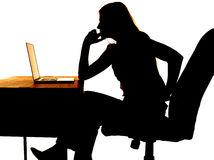 Silhouette woman thinking computer. Silhouette of a woman sitting at a desk with a computer thinking Royalty Free Stock Photo