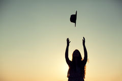 Silhouette of woman throwing her hat in the air Royalty Free Stock Photo