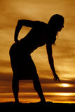 Silhouette of a woman in tight dress bend down Stock Photography