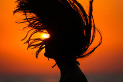 Silhouette of woman tossing hair at sunset Stock Photography
