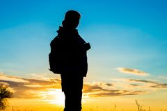 Silhouette of woman tourist over sunset sky royalty free stock image