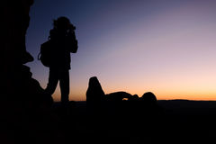 Silhouette of woman traveler shooting camera sunset Stock Images
