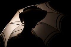 Silhouette woman with an umbrella. Stock Photos