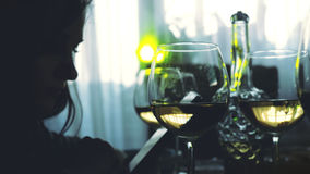 Silhouette of woman uses smartphone and glasses of white wine sits at served table. Stock Photos