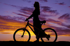 Silhouette of a woman walking with a bike Royalty Free Stock Images