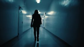 Silhouette of a woman walking down a dark corridor in the late evening. A view from the back of a young woman walking down a dark corridor in the late evening stock footage