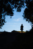 Silhouette of a woman walking on a hilltop Royalty Free Stock Images
