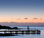 Silhouette of a woman walking on a pier. Silhouette of a woman walking on pier with moon in the sky Stock Photo
