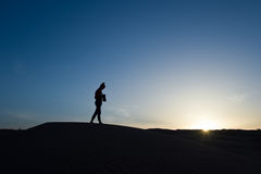 Silhouette of a woman walking in the sunlight Stock Image