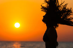 Silhouette of woman waving hair at sunset Royalty Free Stock Images