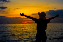 Silhouette women wearing a hat are enjoying a beautiful sunset o Royalty Free Stock Images