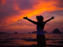 Silhouette of woman wearing hat with open arms. Under the sunrise near the sea Stock Photography