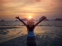 Silhouette of woman wearing hat with open arms under the sunrise. Near the sea Stock Photography