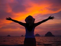 Silhouette of woman wearing hat with open arms. Under the sunrise near the sea Stock Photos