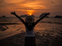 Silhouette of woman wearing hat with open arms under the sunrise near the sea.  Royalty Free Stock Photography