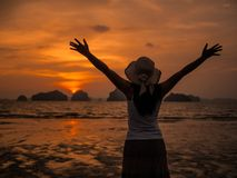 Silhouette of woman wearing hat with open arms under the sunrise near the sea. Summer concept Royalty Free Stock Photo