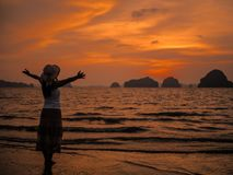 Silhouette of woman wearing hat with open arms under the sunrise near the sea. Summer concept Royalty Free Stock Image
